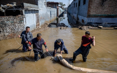 Rescuers drain off flood waters after heavy rainfall at a flooded area in the city of Jinzhong